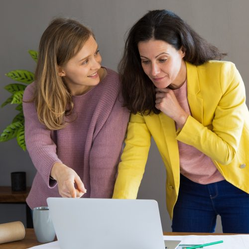 Two young female professionals discussing exciting information they found on a laptop.