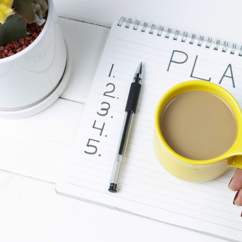 Closeup of a notepad with a 5-step marketing plan written on it.