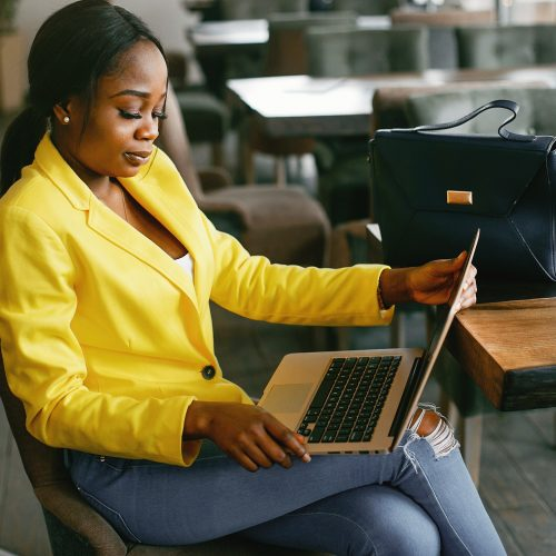 Stylish businesswoman reviewing business metrics on a laptop.