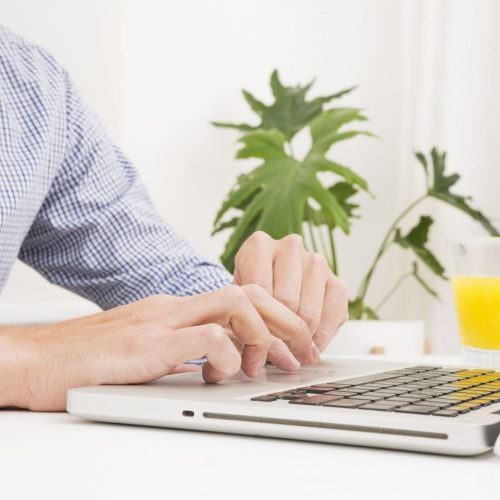 Man typing website copy in the morning on his laptop.