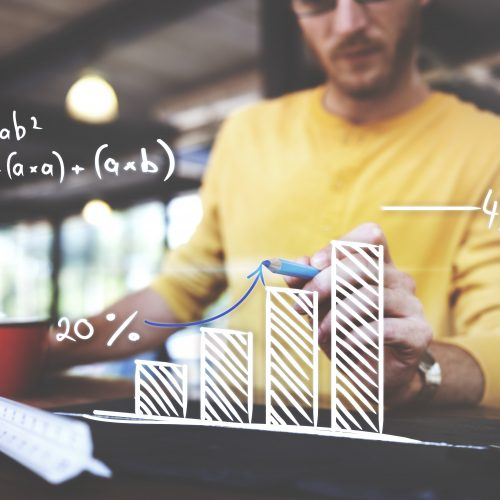 Man analyzing marketing metrics using whiteboard bar graph.