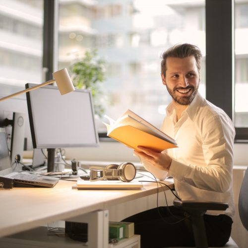 Smiling businessman sitting at a computer