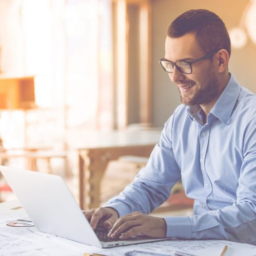 Smiling businessman reviewing a website copywriting project.